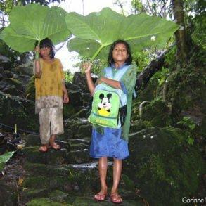 Deux fillettes s'abritent sous de grandes feuilles, en guise de parapluie. Philippines, février 2008.