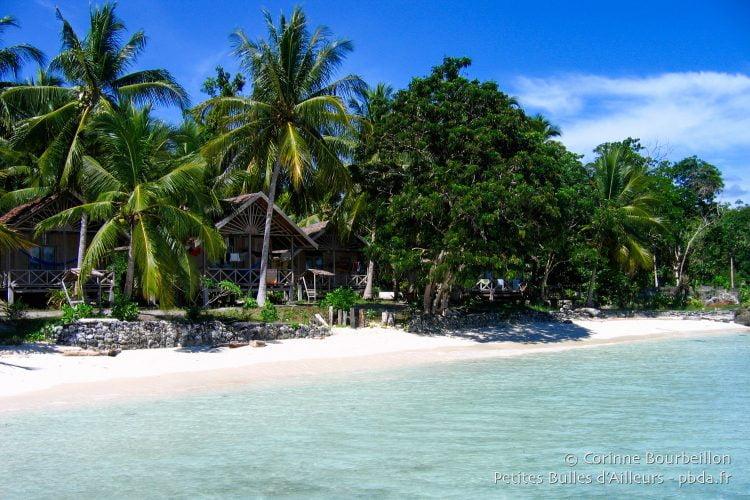 Island Retreat : les bungalows de bois s'alignent à l'ombre des cocotiers devant la plage. (Togian Islands, Sulawesi, Indonésie, juillet 2007.)