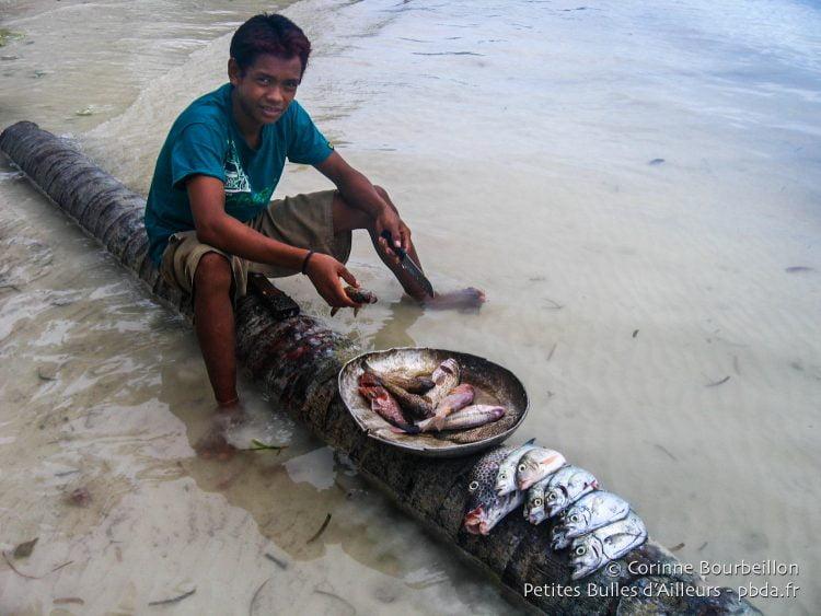 Island Retreat : écaillage des poissons du dîner sur la plage. (Togian Islands, Sulawesi, Indonésie, juillet 2007.)