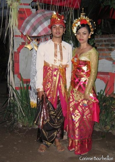 The bride and groom pose, a little frozen, in their sumptuous ceremonial clothes. Pemuteran, Bali. July 2008.