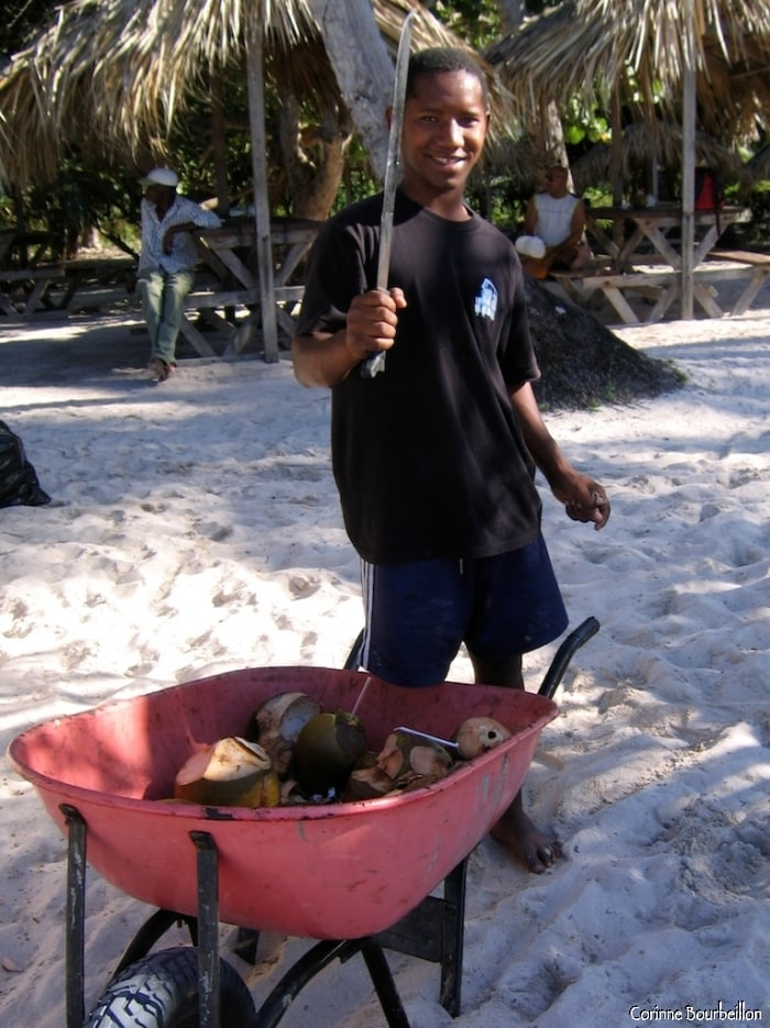 The young coconut seller proudly brandishes his machete for my purpose.