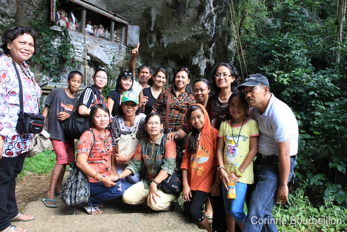 Look for the intruder ... Photo session with a group of Indonesian tourists at the Londa site. Toraja Country, Sulawesi, Indonesia. July 2010.