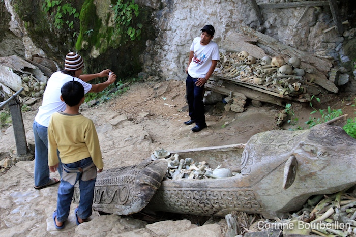 Site funéraire de Londa. Le grand jeu consiste à se prendre en photo devant les ossements. Pays Toraja, Sulawesi, Indonésie. Juillet 2010.