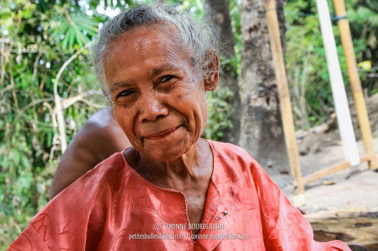 La vieille dame s'arrête de tisser un instant pour me faire un grand sourire, bouche fermée, évitant de montrer à mon objectif ses gencives et ses dents rougies par la noix d'arec que mâchent ici tous les anciens. (Flores, Indonésie, juillet 2011)