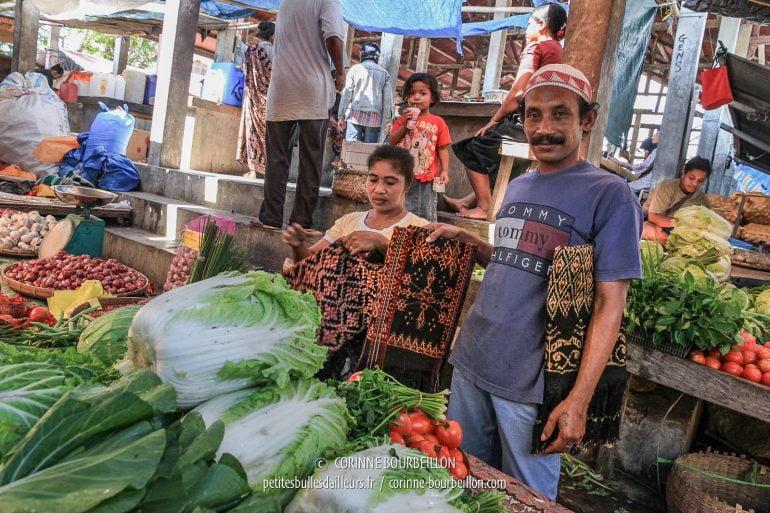 Marchand d'ikat derrière les étals de légumes au marché de Maumere. (Flores, Indonésie. Juillet 2011)