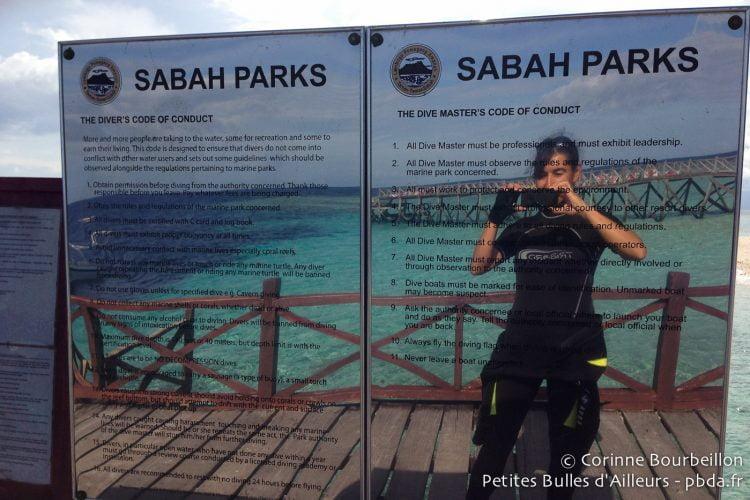 Des panneaux sur le ponton de Sipadan rappellent les règles à observer dans la réserve marine de l'île. Bornéo, Malaisie, juillet 2013.