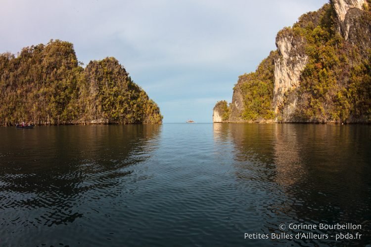 On the horizon, between the cliffs, we see another dive cruiser. (Misool, Raja Ampat, West Papua, Indonesia, November 2015.)