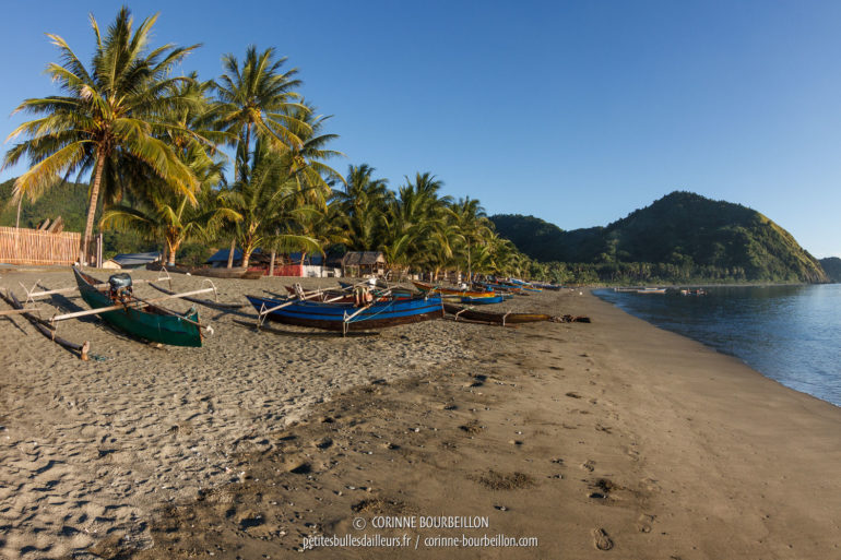The fishing boats on the gray-black sand beach of Kampanar village. (Sulawesi, Indonesia, July 2017)