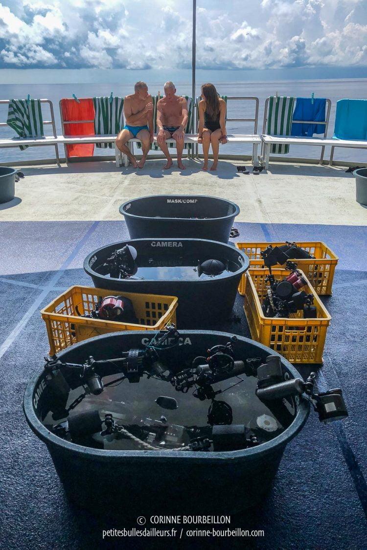 Les appareils photos, au frais dans des bacs d'eau, attendent la prochaine plongée. (Tubbataha, Philippines, mai 2018)