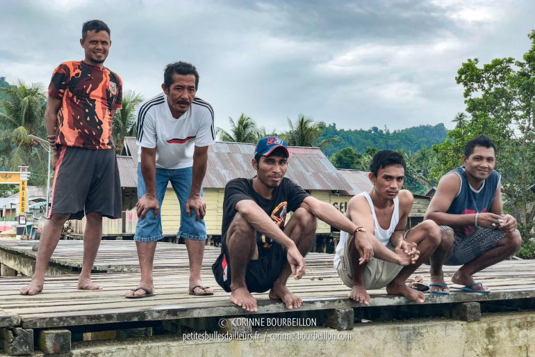Under a gray sky, the guys from the neighboring village watch me with a smile wedge draw my iPhone for a souvenir photo. Today it's muck-dive under their pontoon. (Sali Islands, Halmahera, Indonesia, July 2018)