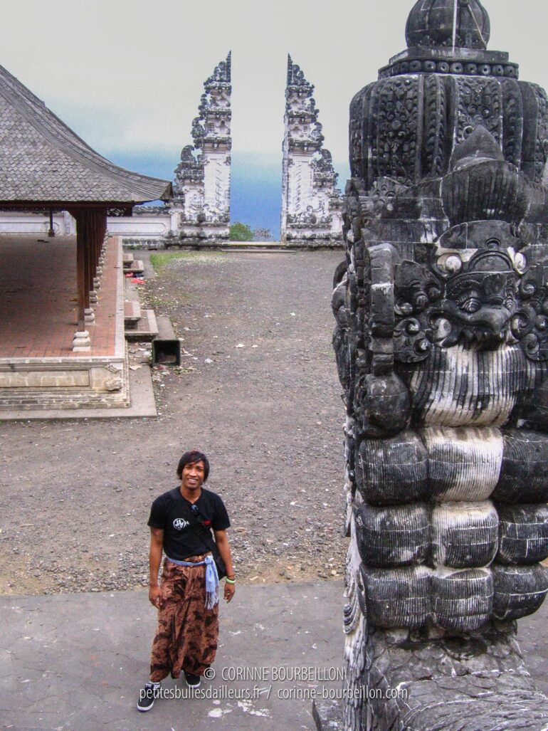 Sana poses at the foot of the steps, in front of the slit door of the temple. Pura Lempuyang, Amed and Amlapura area. (Bali, Indonesia, July 2008)