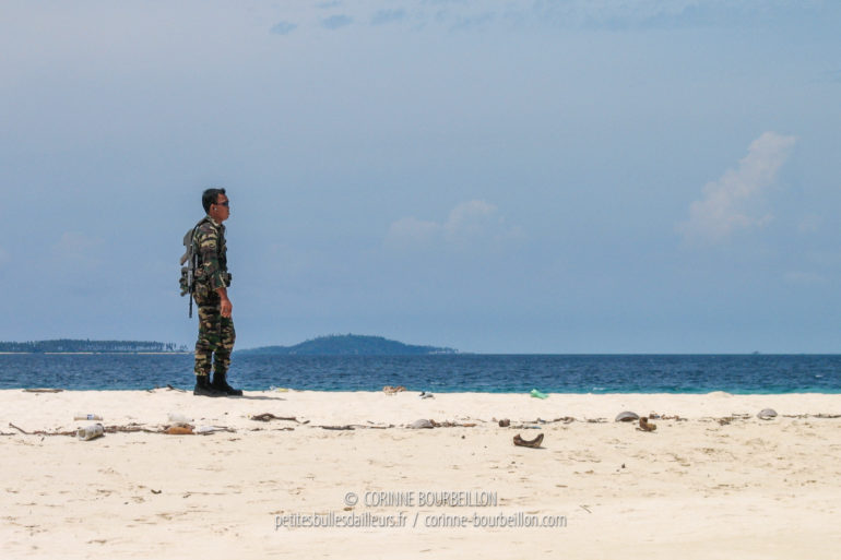 A lattice Malaysian soldier stands guard on the sand of Sibuan. (Borneo, Malaysia, July 2006)