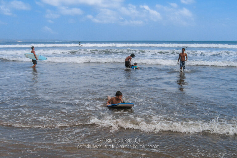 Kids from Bali as well as foreign tourists enjoy the waves of Kuta Beach. (Indonesia, July 2008)