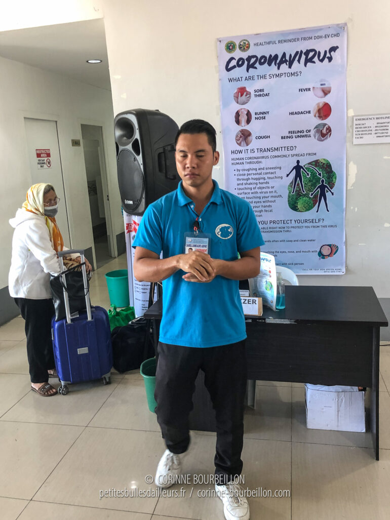 In the NAIA3 home terminal, a poster on the coronavirus is displayed on the wall. An elderly passenger is wearing the mask, but not this employee from the airport. (Philippines, February 2020)